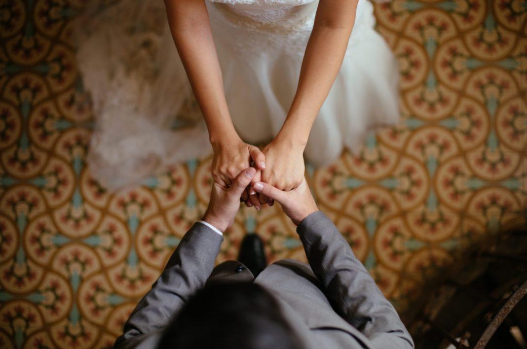 Femme avec une robe de mariée tenant les mains d'un homme en costume